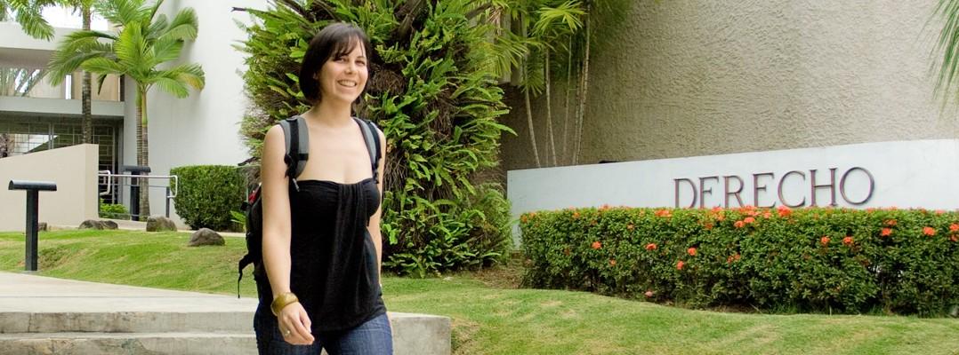 Una estudiante caminando por los espectaculares jardines de la Escuela de Derecho